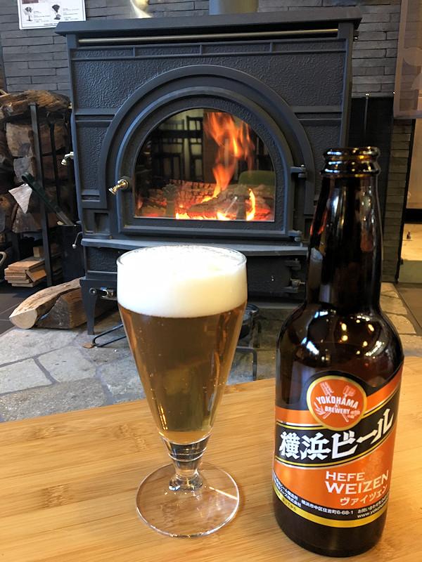 薪ストーブの美しい炎の前に、キンキンに冷えた横浜ビール・ヴァイツェンとグラス