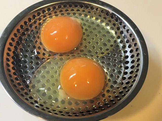 平ざるに卵2個を落とした様子