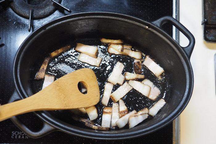 鉄鍋でベーコンを炒める様子